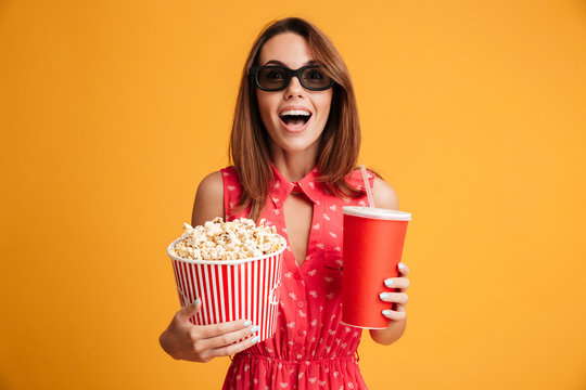 Close-up portrait of happy exited woman in 3d glasses holding cola and popcorn, looking at camera