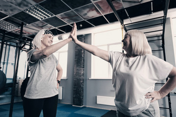 Two senior women high-fiving each other in gym