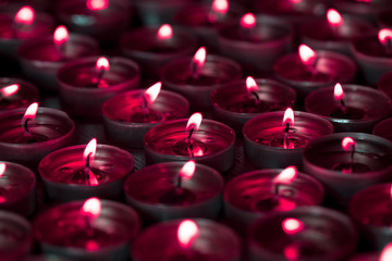 Spooky blood red candlelight from lighted tea light candle flames. Trick or treat halloween background lighting
