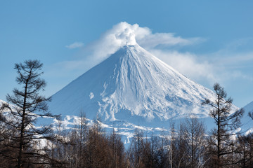 Winter volcanic landscape of Kamchatka Peninsula: view of eruption active Klyuchevskoy Volcano in sunny day clear weather. Eurasia, Russian Far East, Kamchatka Region, Klyuchevskaya Group of Volcanoes
