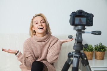 Blogging concept. Young female blogger next to video camera at home. Young woman recording vlog on her video channel.