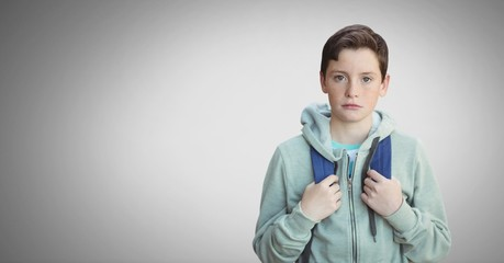 Boy against grey background with bag