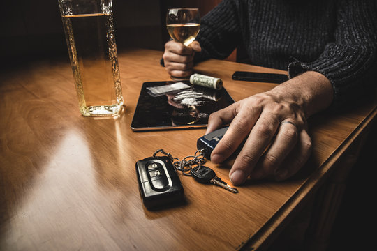 Man takes car keys after using cocaine drug and drinking whiskey. Drugs, alcohol and driving concept