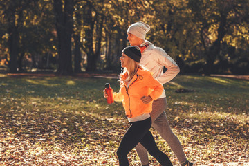 Couple of runners jogging a the city park.Autumn and cold weather.