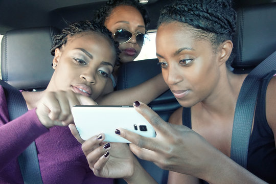 3 young women in back seat checking social media on cell phone