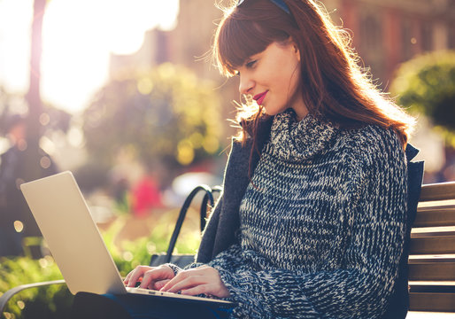 Woman using laptop outdoor sitting in the city street, urban scene