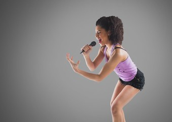 Young woman singing with microphone against grey background