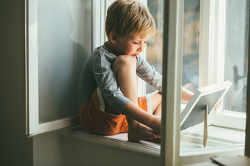 Sad rose cheeks barefoot smiling preschooler boy dressed home clothes sitting on windowsill and looking on foto in the frame.