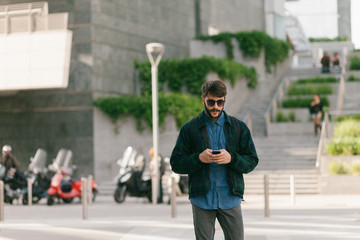 Young man walking and typing at his cellphone