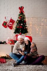 Young cheerful smiling couple with Santa hats looking on a tablet while sitting on the floor for Christmas holidays.