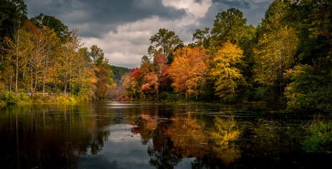 Vibrant autumn foliage reflected in Swartswood Lake at Swartswood Lake State Park, Stillwater, New...
