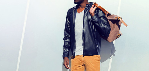 Fashion african man in a black leather jacket holds a bag in the city on a gray background Wall mural
