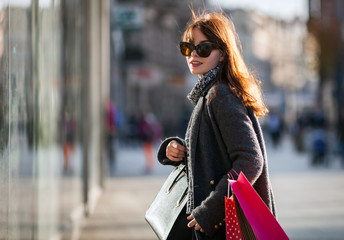 Woman during walk on street with shopping bags