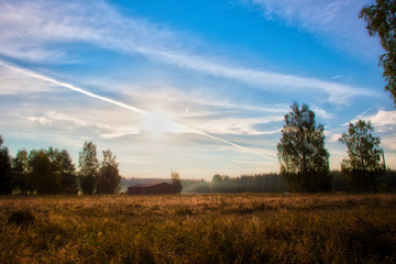 Landscape - morning in the field, the sun, the house.