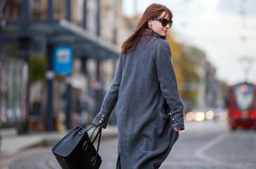 Trendy fashion woman in coat walking on the street, city scene Wall mural