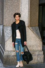 Man Casual Fashion. American college student traveling, working in New York, wearing fashionable long coat, jeans, boots,  carrying hand bag, standing by column on street. Instagram filtered effect..