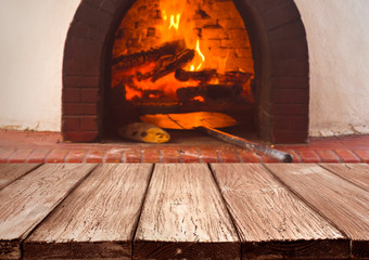 Vintage wooden planks over blurred traditional stove for baking pizza