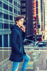 American college student studying in New York, wearing fashionable long coat, jeans, standing by railing on balcony, facing street with high buildings, talking on cell phone. Instagram filtered effect