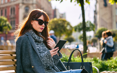 Pretty woman using tablet or ebook reader sitting in town, urban scene