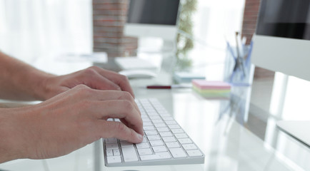 close-up of an employee typing on a personal computer keyboard.