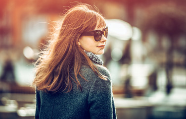 Close up fashion portrait of trendy woman in coat at the city Wall mural