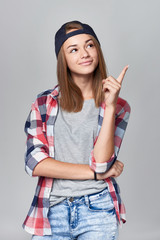 Teen girl in baseball cap pointing to the side up at empty copy space, over grey background.