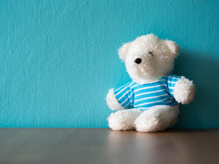 The white teddy bear wear a blue shirt and sitting on wood table. the background is turquoise copy space for content