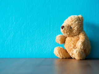 The brown teddy bear sitting on wood table. the background is turquoise and copy space for content