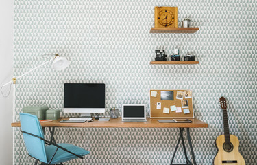 Office workspace with desk and computer against wallpaper