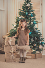 Young brunette dolly lady girl stylish dressed cozy warm winter gray jacket with fur posing sitting standing in studio close to Christmas New Year tree and presents.