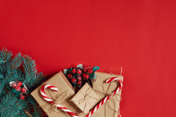 Fir branch and gift box on red background