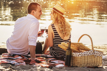 Celebrating their special date. Rear view of beautiful young couple drinking wine and looking at each other while having romantic picnic on the beach.