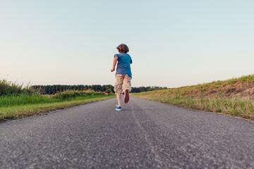Boy running away on a long road in the fields