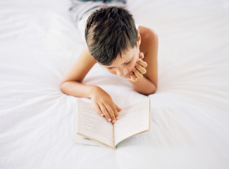 Boy lying in bed reading a book