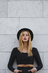 Portrait of edgy girl in black agains a grey wall (french style)