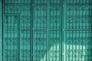 Blue/turquoise decorative metal door/entrance; abstract pattern background