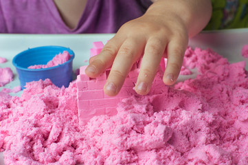 Close up of childs hand playing with pink kinetic sand
