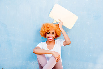 Beautiful african woman holding colorful thoughtful bubble on the blue wall background