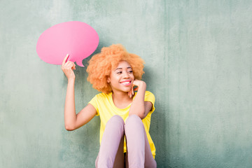 Beautiful african woman holding colorful thoughtful bubble on the green wall background