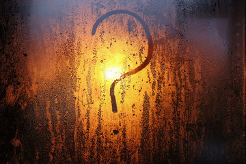 drawing in the form of a question mark on the sweaty glass of the window