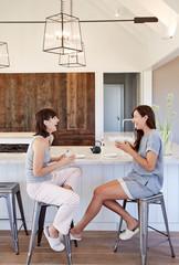 Friends having tea in kitchen of modern design farmhouse