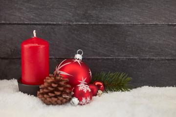 Rote Kerze vor Holz auf Schnee zu Weihnachten