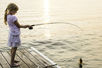 Girl Catching Sunfish Fishing From Cottage Dock in Summer
