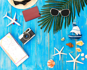 Summer  accessories, camera and sunglasses go to travel in the beach. Tropical sea.Unusual top view. Travel and Summer Concept.
