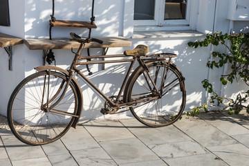Altes Fahrrad lehnt an weißer Wand