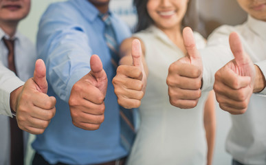 Cheerful business group giving thumbs up. Group of happy multiracial businesspeople gesturing thumb up sign. Wall mural