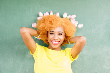 Colorful portrait of a beautiful african woman holding a bouquet of tulips on the green wall background