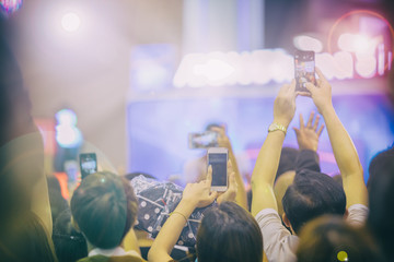 Asian  women holding smart phone and tapping screen for taking pictures on Crowd at concert stage lights,blurry background.