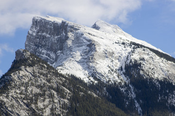 On a fall day, a light layer of snow covers Mount Rundle in Banff National Park, Alberta, Canada.