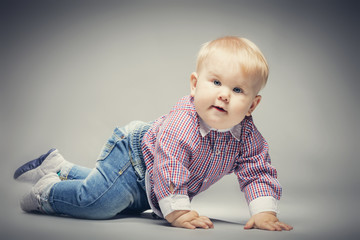 Little blond baby boy crawling on the ground.